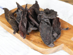Deer-Venison jerky on a white table with a cutting board