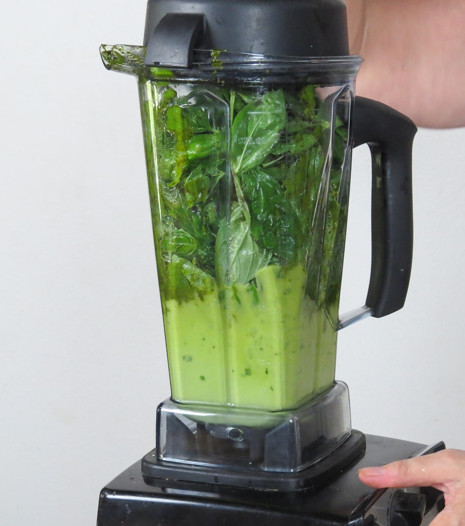 vita mix blender full of basil and other ingredients