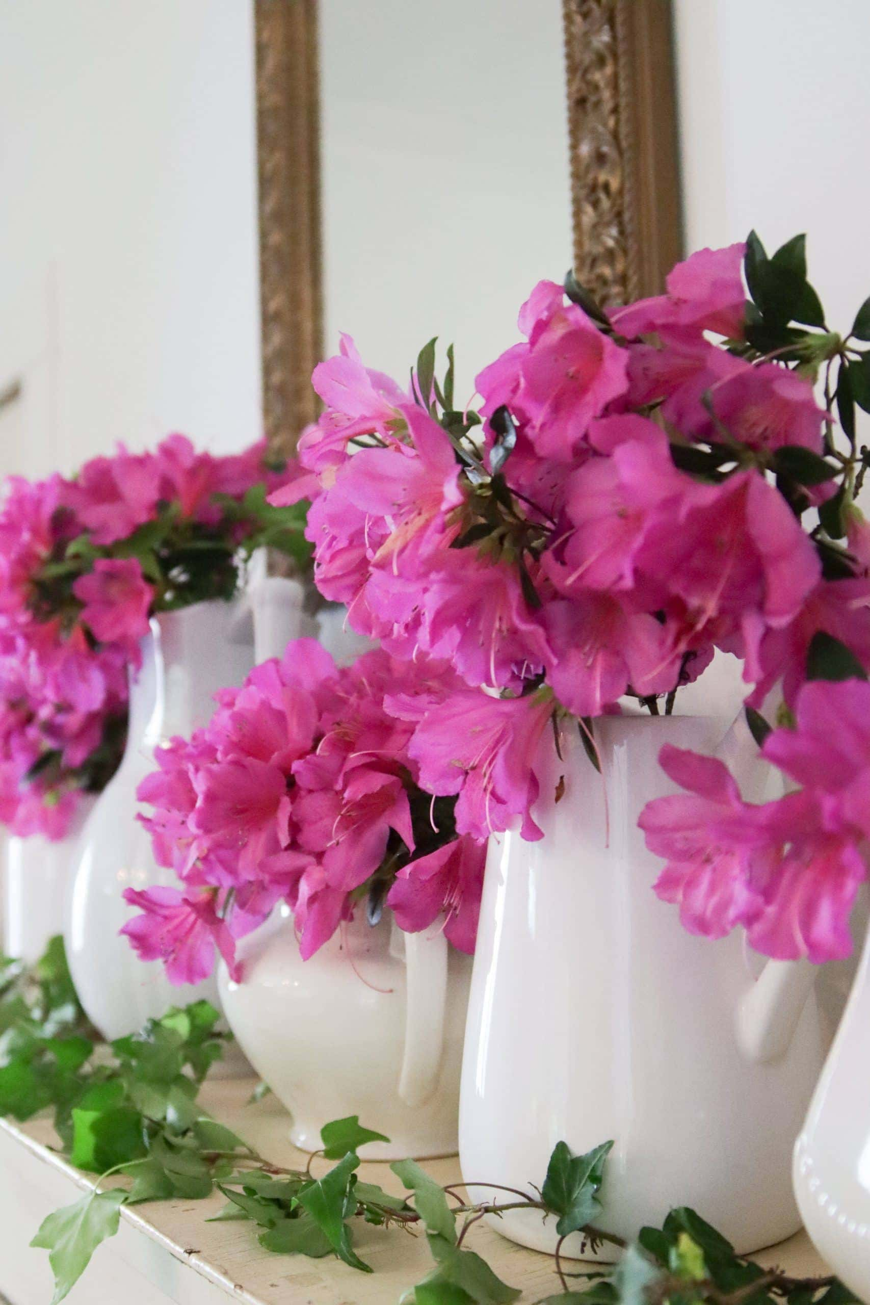 White pitchers with pink flowers on the spring dining room mantle.